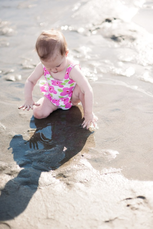 baby in pink suit playing in tidal pool
